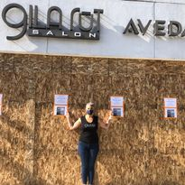 Keri Davis-Duffy, stands in front of her boarded-up Gila Rut location that is plastered with...
