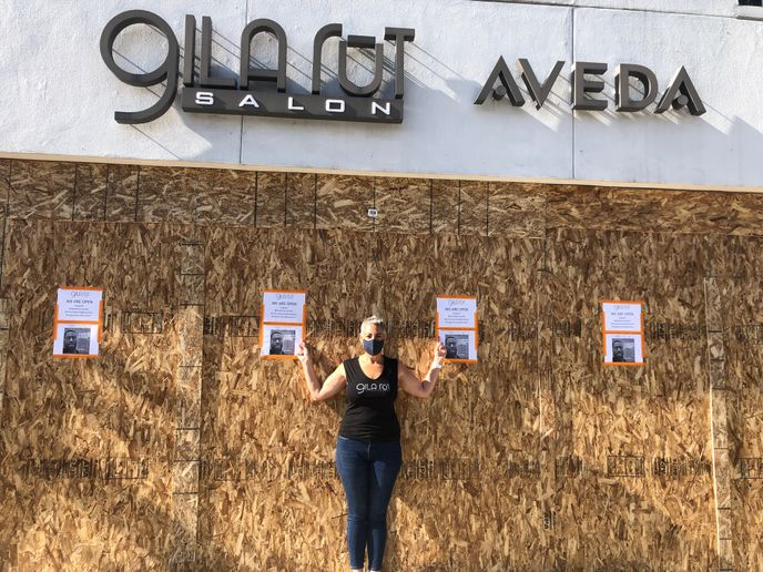 Keri Davis-Duffy, stands in front of her boarded-up Gila Rut location that is plastered with signs announcing the salon is open while simultaneously showing support for George Floyd the peaceful protesters.
