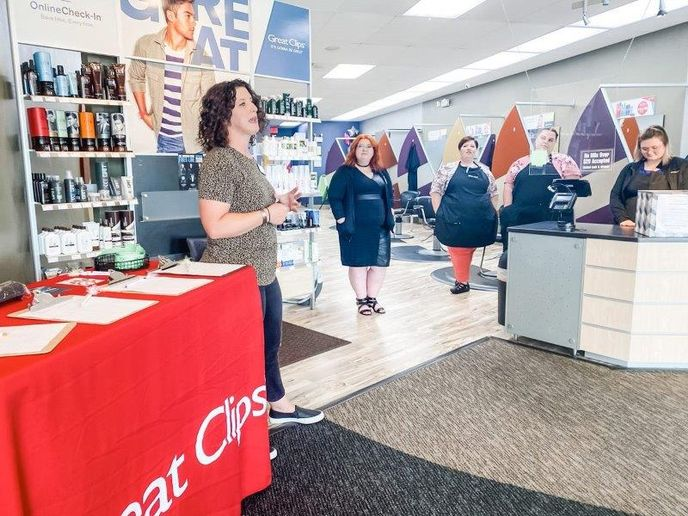 Great Clips' Katie Butler (left) and her team talk to the students about the systems and pay structure that make working for the franchise different than other salons.   - Ivy Boudakian