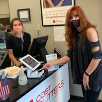 A client uses the Tippy kiosk to tip her stylist at a Cost Cutters location, one of the salons...