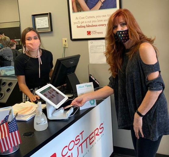A client uses the Tippy kiosk to tip her stylist at a Cost Cutters location, one of the salons that is part of the Alline Salon Group. 