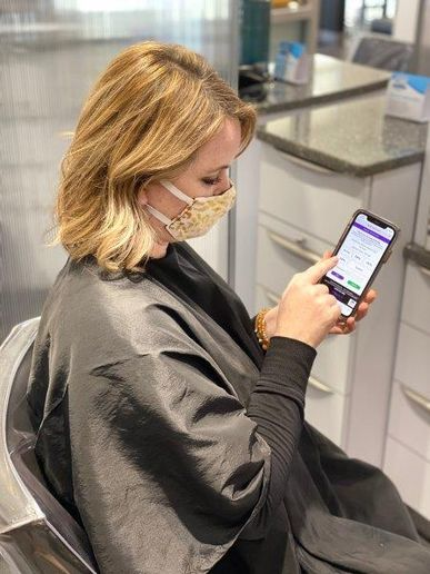 A client at Ginger Bay Salon and Spa in St. Louis, reviews her bill and tips her stylist through Meevo 2's Self-Pay feature.   -