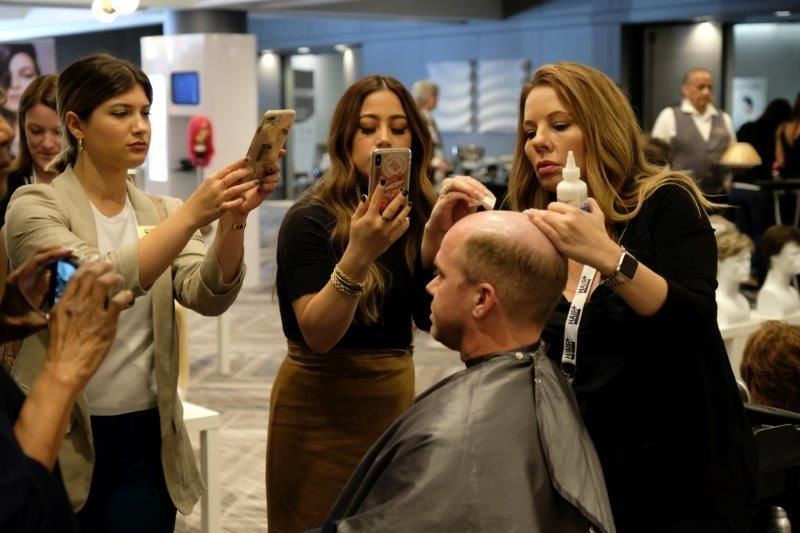 <p>An American Hairlines expert demonstrates how toppers are applied to a male client.</p>
