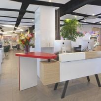 Accent lighting and a bold red color on the desk return give the reception area of Currie Hair...