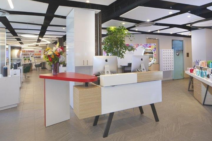 Accent lighting and a bold red color on the desk return give the reception area of Currie Hair Skin and Nails energy and excitement.   -